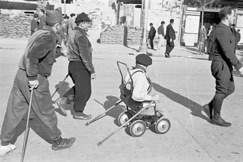 Soldados heridos descansan en la retaguardia, en primer plano aparece uno de ellos con las piernas amputadas y montado en un carrito.